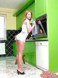 Raunchy redheaded babe strips and creams her boobs in the kitchen