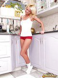 Smiling blonde cutie spreading cream on her divine breasts in the kitchen